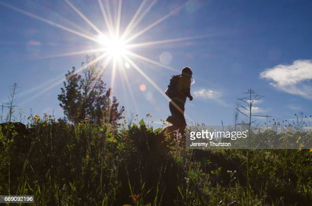 man trail running through mountains on summer day with solar flare