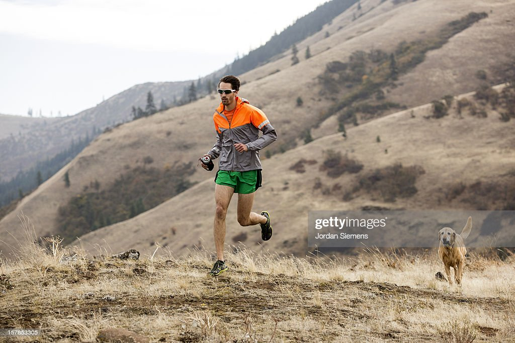 A man trail running with his dog. : Stock Photo
