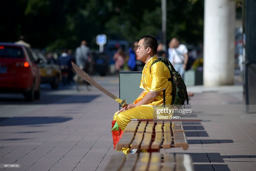 A man training in martial arts rests on a bench along a business street in Beijing on September 24, 2013. The seven-day holiday built around China's National Day on October 1 sees millions of members of China's newly wealthy and mobile middle-class travel locally and abroad.