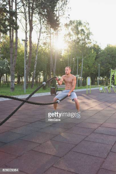 Man training with battle ropes in alternating waves style outdoor