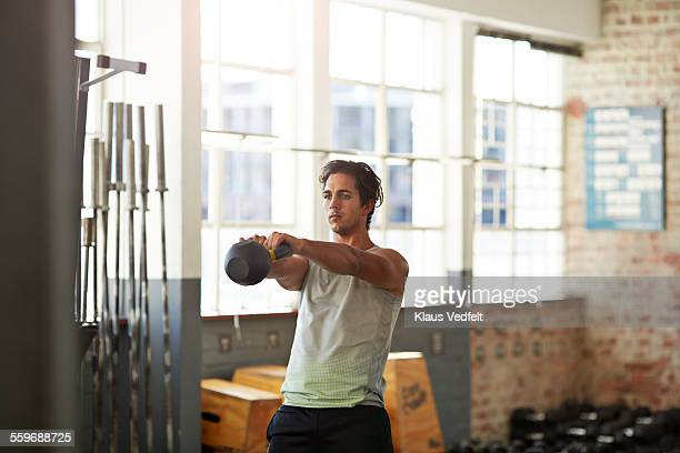 Man training with kettlebell at gym gym