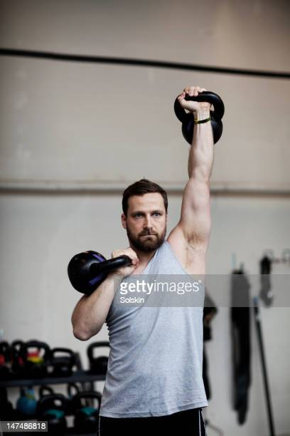 man training with kettlebells in gym