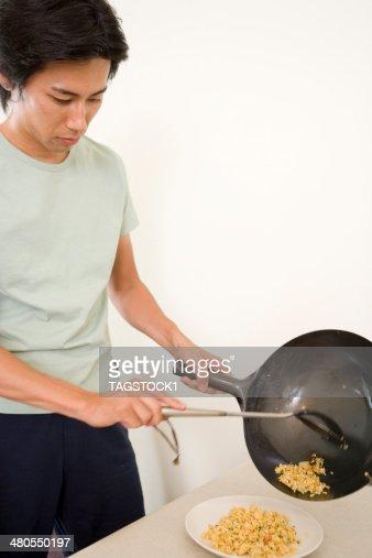 Homem transfering Arroz frito no prato : Foto de stock
