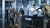 Man with bag of arms trying to pass illegally control point in airport being detained by guards.