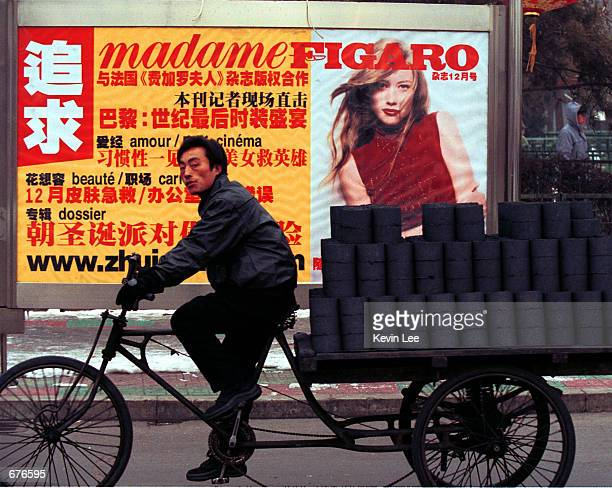 A man transporting a load of coal bricks passes by a billboard featuring an advertisement for a French magazine January 12 2001 in Beijing China...