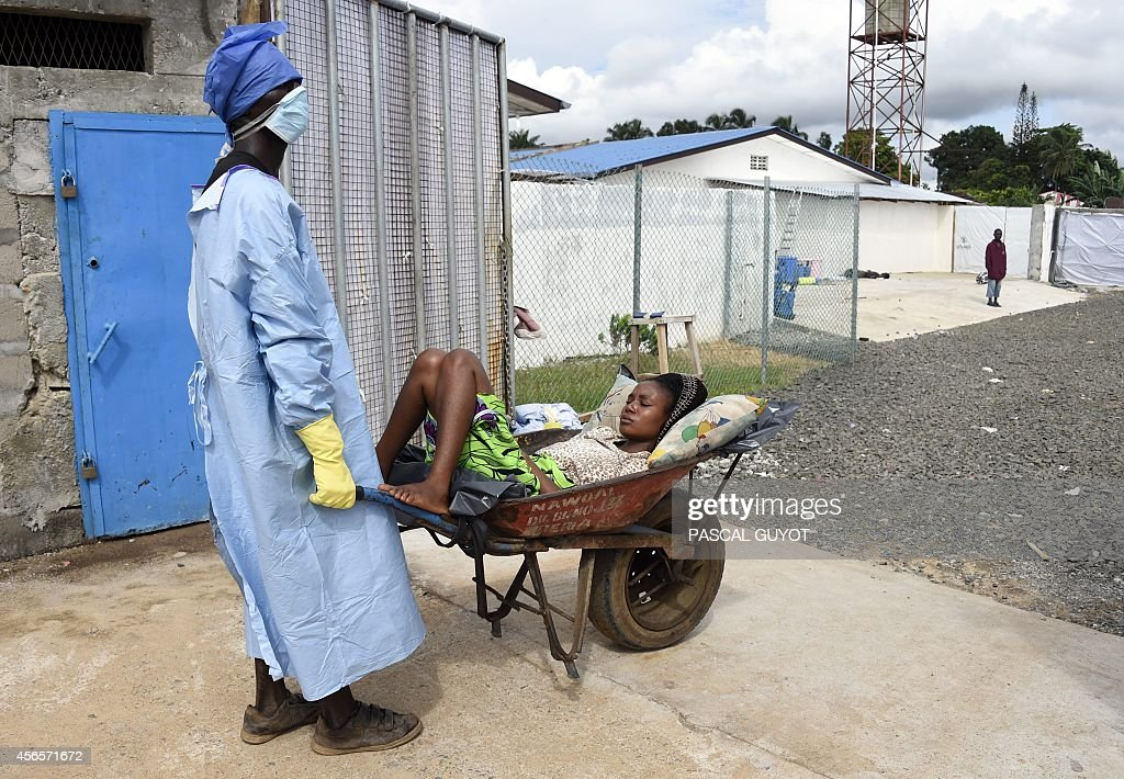 A man transports a possible victim of the Ebola virus in a wheelbarrow on October 2 2014 at the Ebola treatment center at Island hospital in Monrovia...