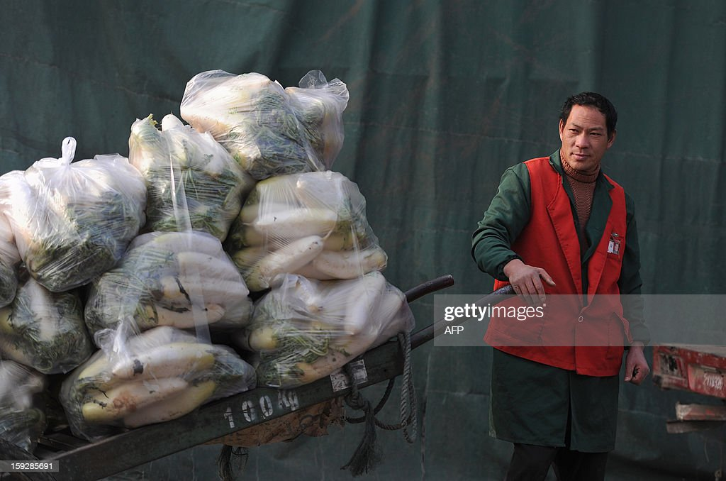 A man transports vegetables in a market in Hefei, central China's Anhui province on January 11, 2013. China's inflation rate slowed sharply in 2012, official data showed on January 11, but analysts warned of increasing price risks this year that may limit scope for measures to boost economic growth. CHINA