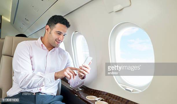 Man traveling by plane and texting on his phone