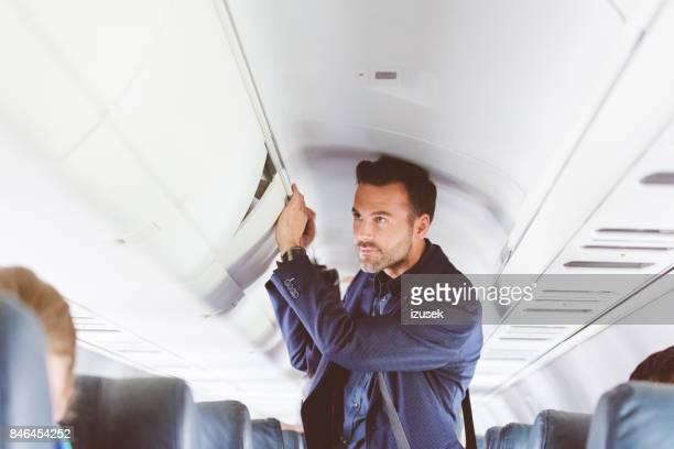 Man travelling by flight storing handbag in overhead locker