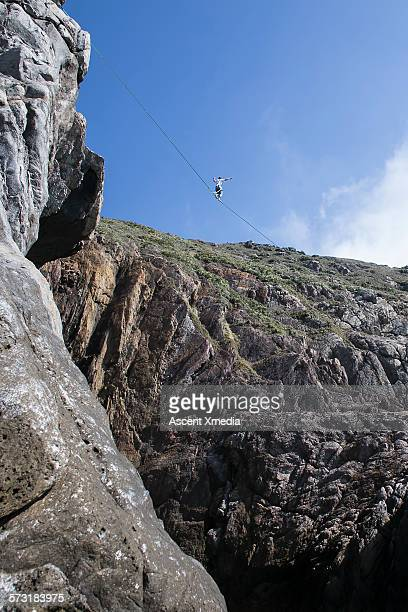 Man traverses highline above rocky cliffs, valley