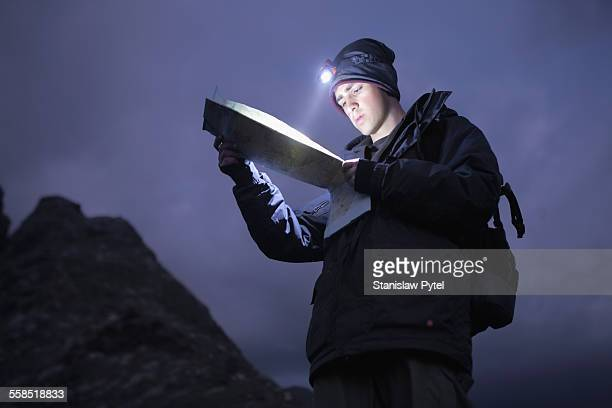Man trekking at night in mountains, looking at map
