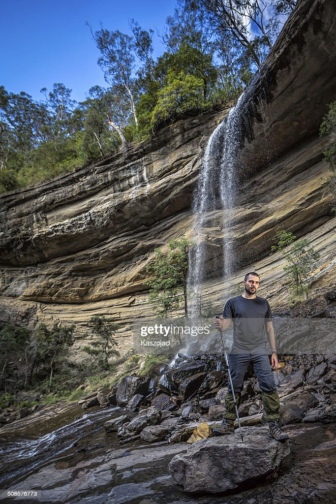 Man trekking on a rocky hill with a waterfall : Stock Photo