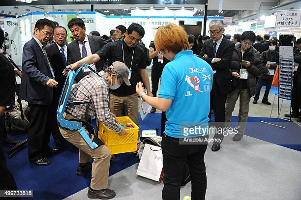 A man tries a welfare robot during the international Robot exhibition 2015 at Tokyo Big Sight Japan on December 3 2015