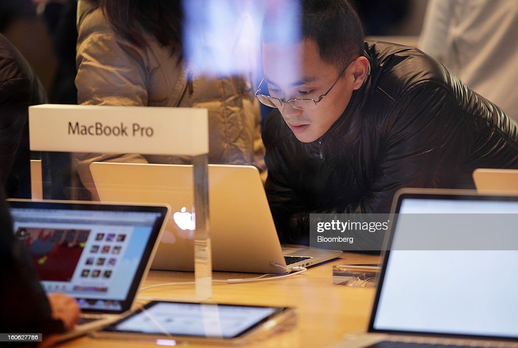 A man tries an Apple Inc. MacBook Pro laptop computer in an Apple store in the East Nanjing Road shopping area of Shanghai, China, on Friday, Feb. 1, 2013. China's services industries grew at the fastest pace since August as gains in retailing and construction aid government efforts to drive a recovery in the world's second-biggest economy. Photographer: Tomohiro Ohsumi/Bloomberg via Getty Images