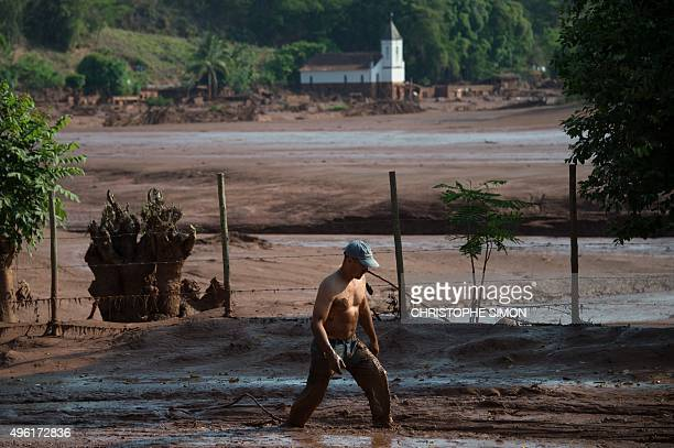 A man tries cross a muddy area of Gesterio part of the Barra Longo city 60 km from Mariana Brazil on November 07 2015 Rescuers searched for a third...