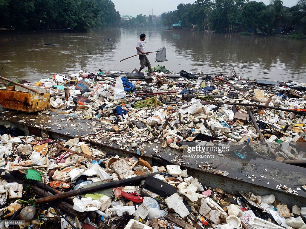 A man tries his fortune by collecting stuck garbage in Jakarta on January 18, 2013 washed together by massive seasonal floods in the Indonesia capital. Floods in Indonesia's capital Jakarta have left at least 11 people dead, authorities said on January 18 as murky brown waters submerged parts of the city's business district, causing chaos for a second day. AFP PHOTO / Bay ISMOYO