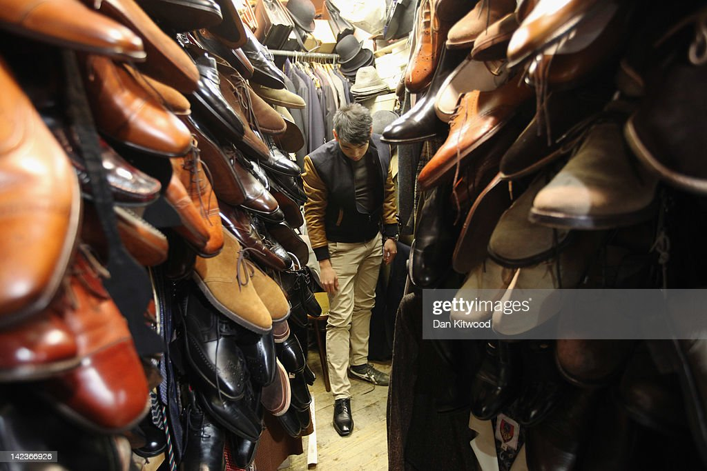 A man tries on shoes in a stall in Camden Market on March 31, 2012 in London, England. Camden in North London has been one of the city's cultural centres since the 1960's, and is home to the famous Camden Market. The borough is rich in musical heritage with a variety of musical and comedy venues, theatres and art galleries.