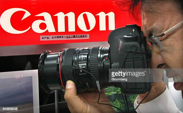 A man tries out a Canon Inc digital camera at an electronics store in Tokyo Japan on Tuesday July 28 2009 Canon Inc the world's largest camera maker...