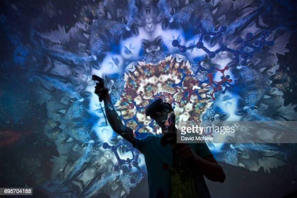A man tries out a Virtual Reality game inside a Fulldomepro 360degree projection dome on opening day of the Electronic Entertainment Expo at the Los...