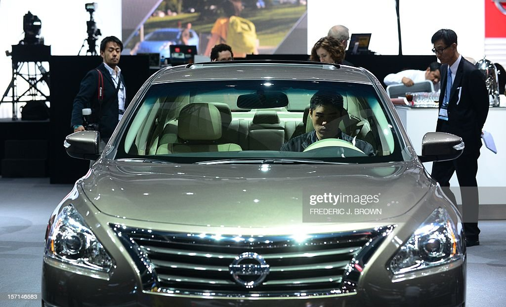 A man tries the driver's seat of a new Nissan Altima displayed on media preview day at the Los Angeles Auto Show on November 28 2012 in Los Angeles...