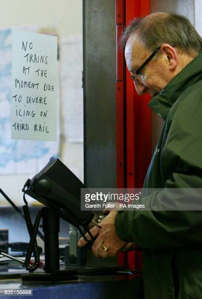 A man tries to buy a ticket at Maidstone East Railway Station in Kent after delays to train services following poor weather conditions