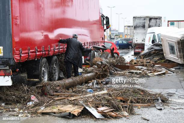 A man tries to clear his truck from trees and waste at a road entrance to the capital Tirana flooded into water after torrential rain blocked it over...