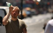 A man tries to cool himself with a bottle of water during the first heat wave of the year June 9 2008 in New York City According to the National...