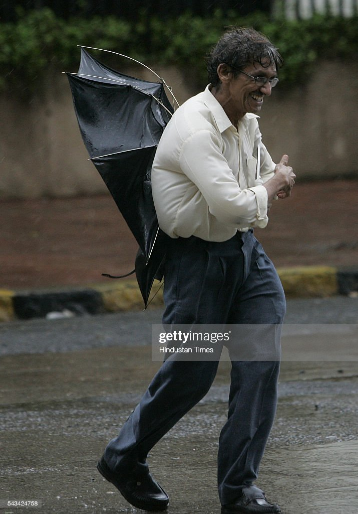 A man tries to get hold his umbrella at Nariman point on August 1, 2005 in Mumbai, India. in Mumbai, India. as whether department predicted storm and heavy rains for next 24 hours.