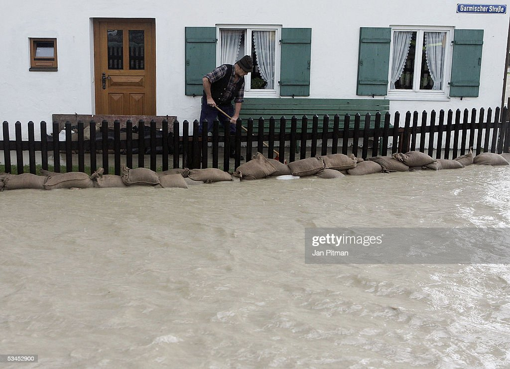 A man tries to protect his house with sandbags on August 23, 2005 in Eschenlohe, Germany. Heavy rainfall and floods in both Austria and Switzerland caused many of the rivers in southern Germany to flood. Half of Eschenlohe town has been evacuated and streets in the whole area are closed to traffic.