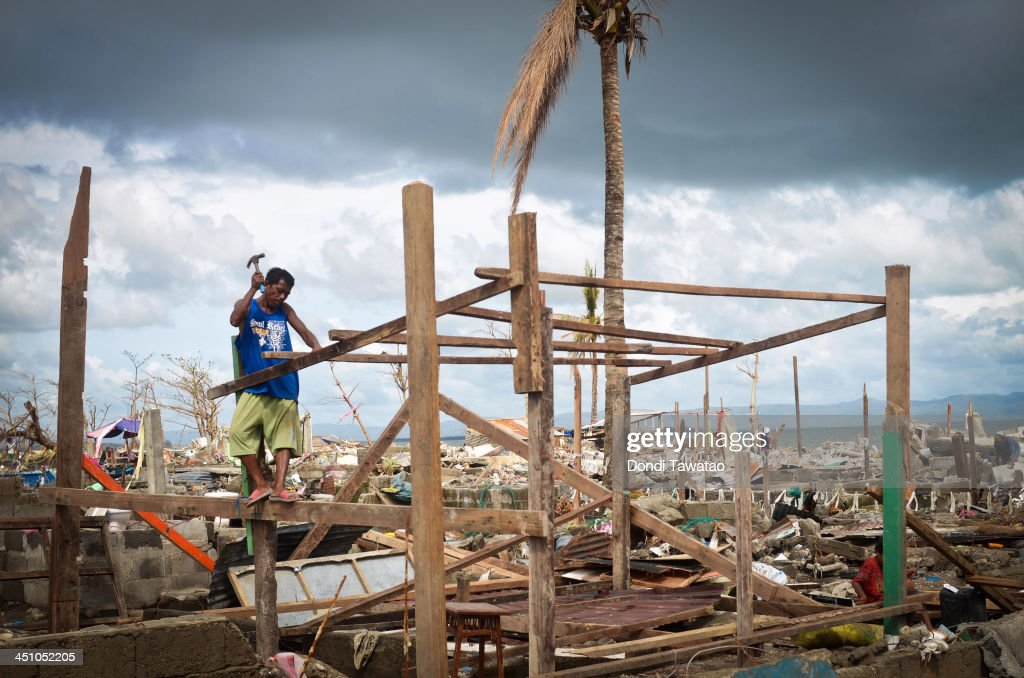 A man tries to rebuild his hut near the shoreline following the recent super typhoon on November 21, 2013 in Tacloban, Leyte, Philippines. Typhoon Haiyan, which ripped through the Philippines on November 9, has been described as one of the most powerful typhoons ever to hit land, leaving thousands dead and hundreds of thousands homeless. Countries all over the world have pledged relief aid to help support those affected by the typhoon, however damage to the airport and roads have made moving the aid into the most affected areas very difficult. With dead bodies left out in the open air and very limited food, water and shelter, health concerns are growing.