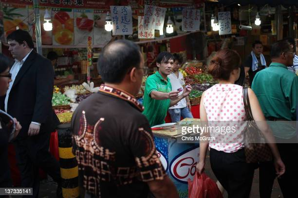 A man tries to sell sweets to pedestrians in Chinatown on January 18 2012 in Singapore On January 23rd Chinese around the world will welcome in the...