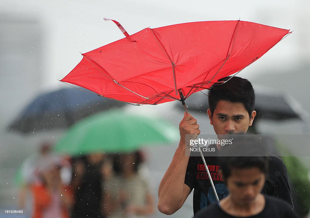 A man tries to shelter under his broken umbrella as he walks on an overpass in the rain in Manila on September 22, 2013. Severe Typhoon Usagi barrelled towards Hong Kong on September 22, shutting down one of the world's busiest sea ports and throwing flight schedules into disarray from Europe to the United States. The storm, described by meteorologists as the most powerful anywhere on Earth this year, killed two people in the Philippines and unleashed landslides in Taiwan en route to Hong Kong.