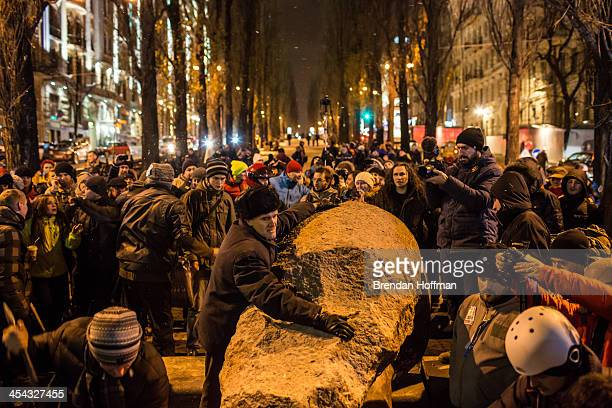 A man tries to stop antigovernment protesters from destroying a statue of Russian communist revolutionary leader Vladimir Lenin on December 8 2013 in...