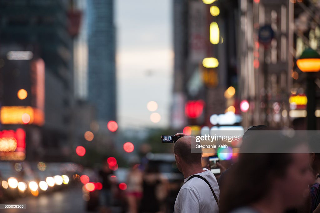 A man tries to take a photo of Manhattanhenge, which was not visible due to clouds, on May 29, 2016 in New York City. Manhattanhenge, an event that happens twice a year, occurs when the setting sun aligns with the east-west streets of Manhattan.