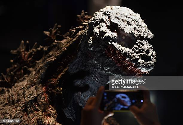 A man tries to take a picture of Godzilla at the Godzilla exhibition in Yokohama suburb of Tokyo to promote latest movie of the monster released in...