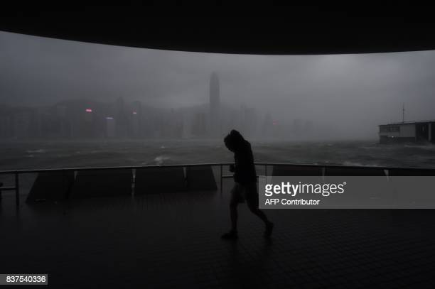 TOPSHOT A man tries to walk along the prominade in Tsim Sha Tsui against winds from Typhoon Hato as dark skies hover over the Hong Kong island...