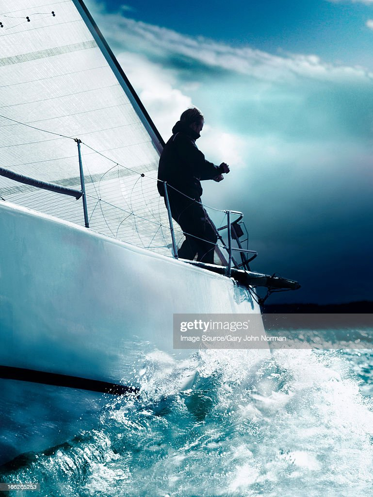 Man trimming sails on yacht in race