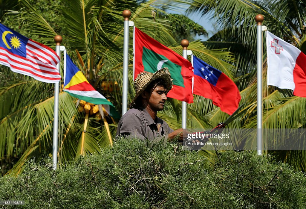 A man trims a hedge in the garden in front of national flags ahead of the Commonwealth Heads of Government Meeting (CHOGM) at Bandaranaike Memorial International Conference Hall (BMICH) on November 9, 2013 in Colombo, Sri Lanka. The bi-annual gathering of Commonwealth leaders will take place in the Sri Lankan captial, Columbo, November 15-17. CHOGM will move forward despite some human rights groups urging leaders to boycott the meetings until Sri Lanka further investigates charges of war crimes. Canadian Prime Minister, Stephen Harper has already confirmed he will not attend.
