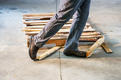 A man tripping over a damaged pallet in a warehouse. Loss prevention and work place safety.