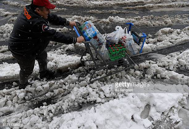 A man try to get his shopping cart to his car as snow continues to fall in Lakewood March 23 2016 The Denver area is under a blizzard warning until 6...