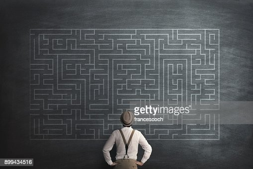man try to solve a labyring on a chalkboard : Stock Photo