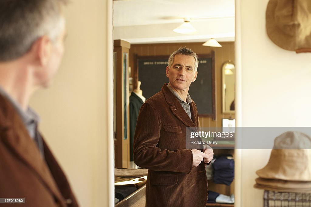 Man trying jacket in made to order clothes shop : Stock Photo
