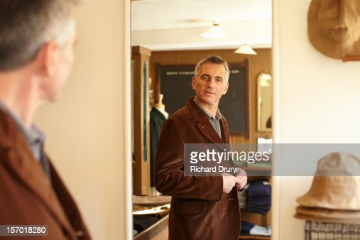 Man trying jacket in made to order clothes shop : Bildbanksbilder