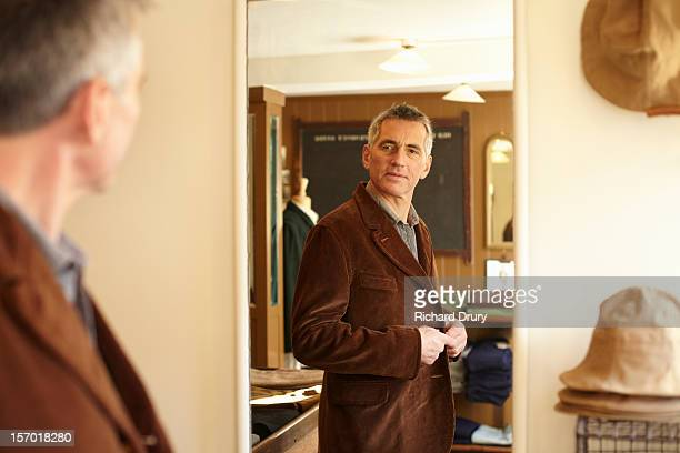 Man trying jacket in made to order clothes shop