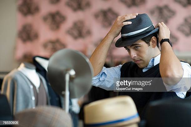 Man trying on hats