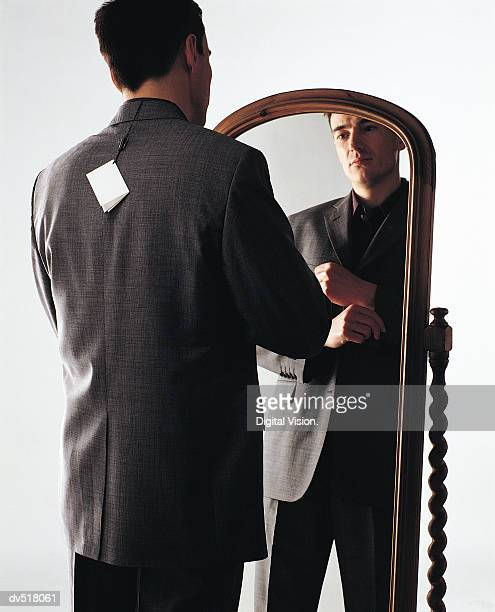 Man trying on suit in front of mirror