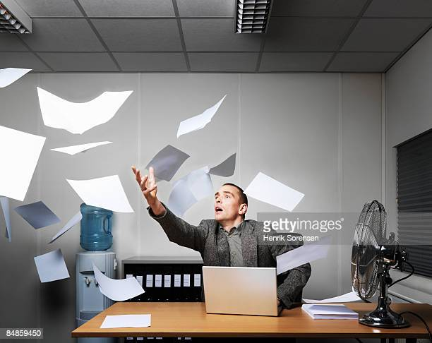Man trying to catch a bunch of flying papers.