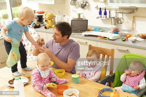 Man trying to feed four babies, two on table