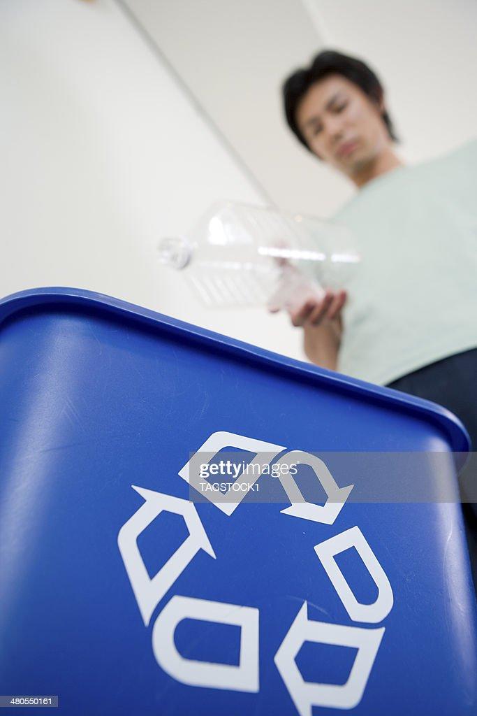 Homem tentando colocar frasco de plástico na caixa COLEÇÃO : Foto de stock