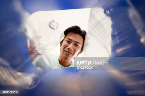Man trying to put plastic bottle into collection box : Stock Photo